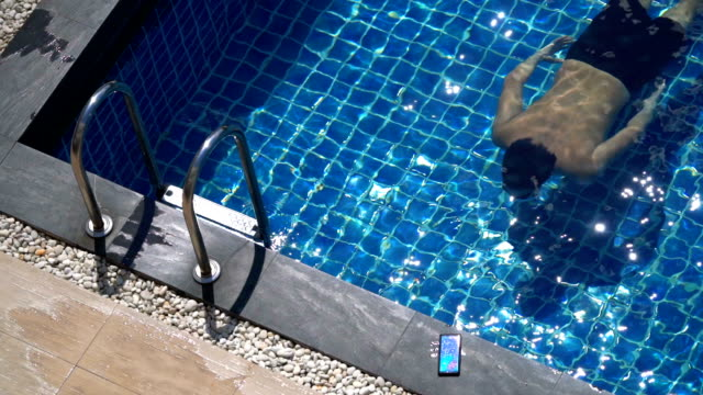 slo mo - asian man swimming to read his text messages from his phone - swimming shorts stock videos & royalty-free footage