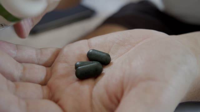 asian man taking the green medicine on hand. - vitamin stock videos & royalty-free footage