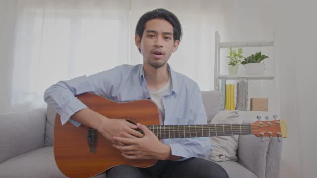 vídeos y material grabado en eventos de stock de hombre asiático enseñando guitarra en línea - enseñar