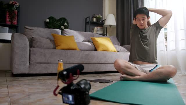 asiatischer mann lehrt oder coaching, um tricep auf dem arm zu seinem online-studenten zu strecken, der zu hause trainiert. vlogger macht einen inhalt für seine live-streaming oder vlog auf social media. - pilates stock-videos und b-roll-filmmaterial