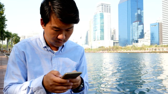 asian man texting on a mobile phone - technophile stock videos & royalty-free footage