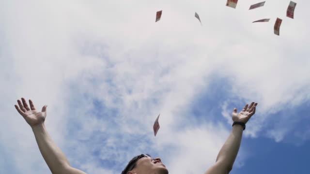 vídeos y material grabado en eventos de stock de slo mo hombre asiático lanzando dinero al cielo - documental imagen en movimiento