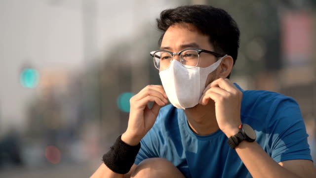 slo mo asian man tie his shoes before running with pollution mask on - inhaling stock videos & royalty-free footage