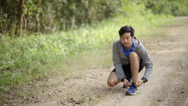asiatischer mann krawatte sportschuh vor start ausführen - menschliches knie stock-videos und b-roll-filmmaterial
