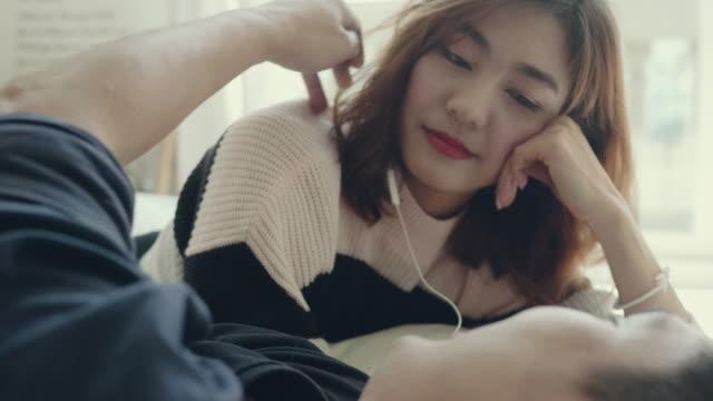 vídeos de stock, filmes e b-roll de homem asiático tocar o cabelo de mulher no quarto. - acariciando