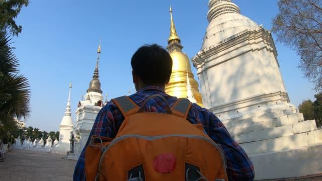 stockvideo's en b-roll-footage met aziatische man toeristische wandelingen in de tempel met zijn rugzak - verwonderingsdrang
