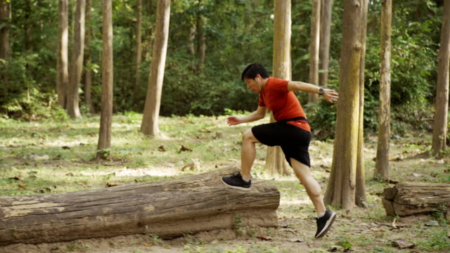 TS Asian man trail running in the forest.