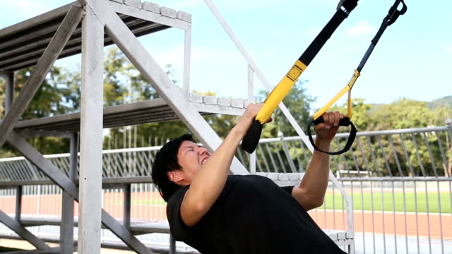 Asian man train his chest by using rope exercise