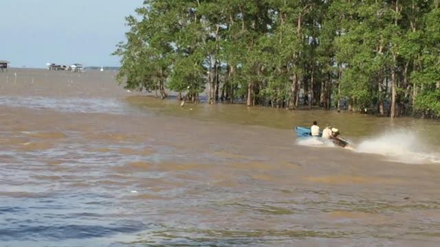 stockvideo's en b-roll-footage met aziatische mensenreis op boot die in tropisch mangrovebos drijft - rondrijden