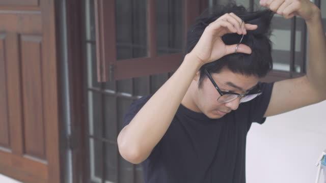 自分の髪をトリミングアジアの男 - 鏡点の映像素材/bロール