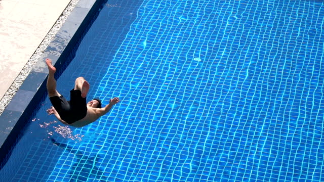 slo mo - asian man trying to do backflip into swimming pool - swimming shorts stock videos & royalty-free footage