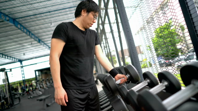 Asian man trying to pick heavy dumbbell in gym