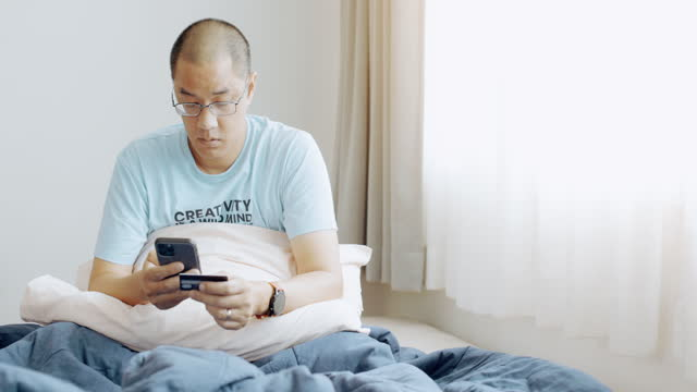 vídeos de stock e filmes b-roll de asian man typing on phone in bedroom. holding credit card. - one mature man only