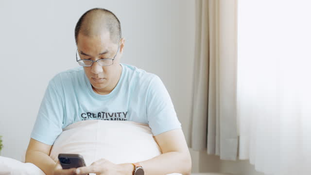 vídeos de stock e filmes b-roll de asian man typing on phone in bedroom. medium shot. - one mature man only