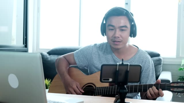 asian man use their notebook computers to study and practice playing guitar on the internet at home - creative occupation stock videos & royalty-free footage