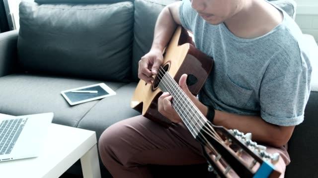 vídeos y material grabado en eventos de stock de hombre asiático utilizar sus computadoras portátiles para estudiar y practicar tocar la guitarra en internet en casa - canto