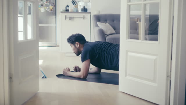 asian man uses digital tablet to learn plank position - domestic life stock videos & royalty-free footage