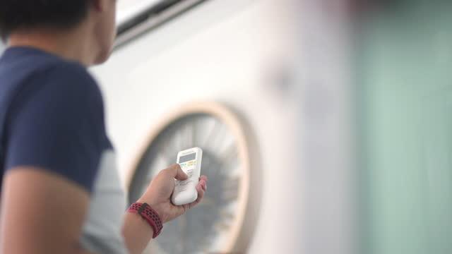 uomo asiatico che utilizza un telecomando e regola la temperatura del condizionatore d'aria a casa - remote control video stock e b–roll