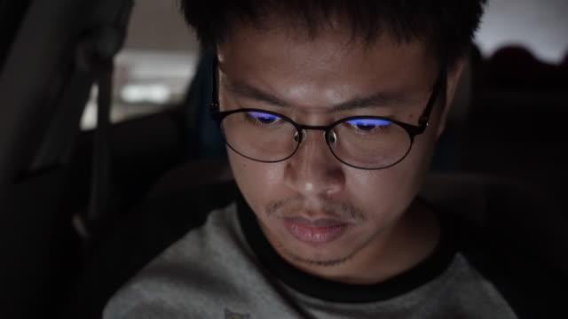 stockvideo's en b-roll-footage met aziatische mens die computer bij nacht gebruikt. - leesbril