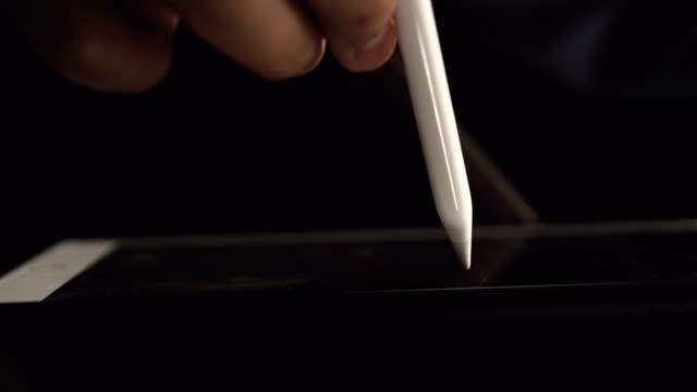 vídeos de stock e filmes b-roll de asian man using digital tablet and pen at home - assinar