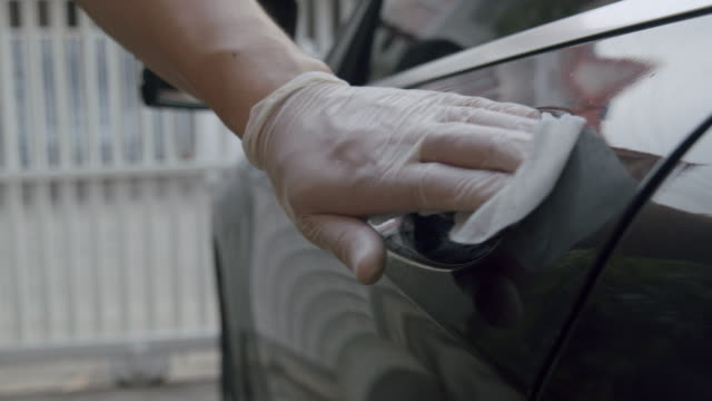 asian man using disinfection wipes cleaning  a car part or doors for cleaning and antibacterial from coronavirus or covid-19 issue in the living room at home. 4k resolution footage - cleaning glove stock videos & royalty-free footage