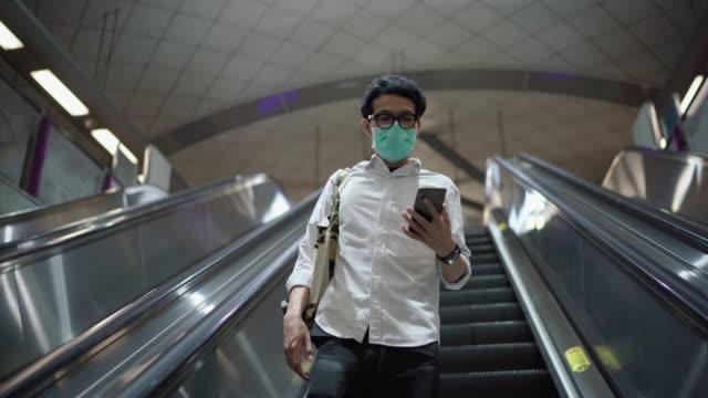 asiatischer mann mit rolltreppe im bahnhof ist leer - öffentliches verkehrsmittel stock-videos und b-roll-filmmaterial