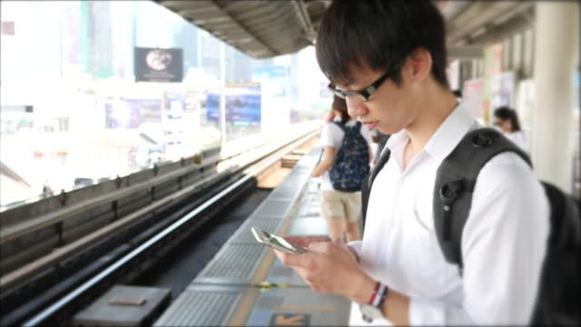 アジア人の男性が列車に近づくと、彼の携帯電話を使用して - 駅点の映像素材/bロール