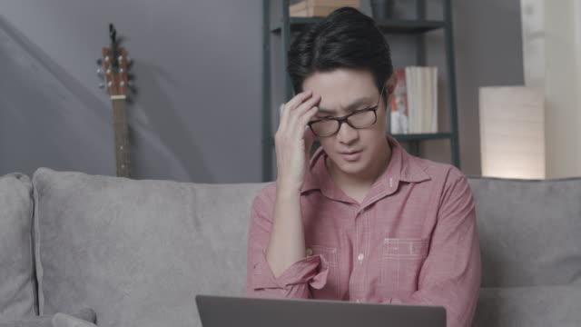 stockvideo's en b-roll-footage met aziatische mens die laptopcomputer gebruikt aan het lezen van online nieuws en het hebben van schok verstoord en mislukking op het terwijl het zitten op een bank in de woonkamer thuis. volwassen mens die thuis terwijl coronavirus quarantaine lockdown situa - geschokt