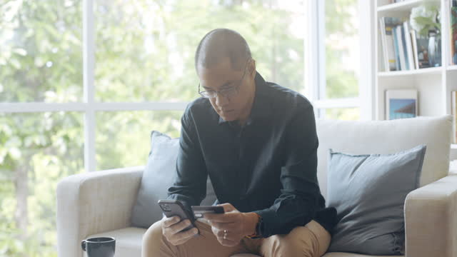 vídeos de stock e filmes b-roll de asian man using mobile phone to make payment. - one mature man only