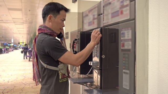 Asian man using public phone at airport