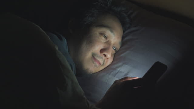 asian man using smart phone on bed at nighttime - staring stock videos & royalty-free footage