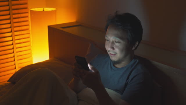 asian man using smart phone on bed at nighttime - ora di andare a letto video stock e b–roll