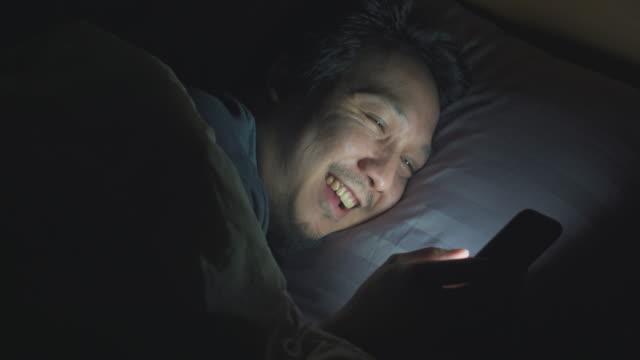 夜間にベッドでスマートフォンを使用するアジア人男性 - 寝る前点の映像素材/bロール