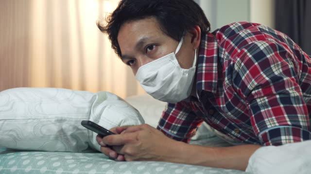 asian man using smart phone on bed self-quarantine for coronavirus - mental health stock videos & royalty-free footage
