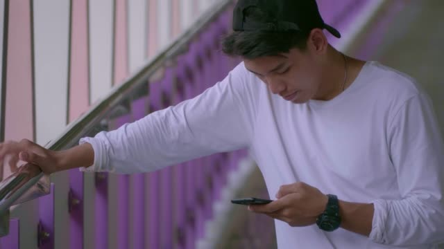 asian man using smart phone on sky walk - only teenage boys stock videos & royalty-free footage