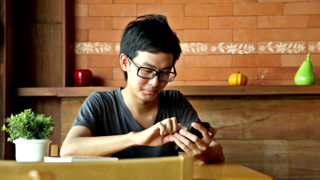 Asian man using smart phone or tablet, waiting for someone