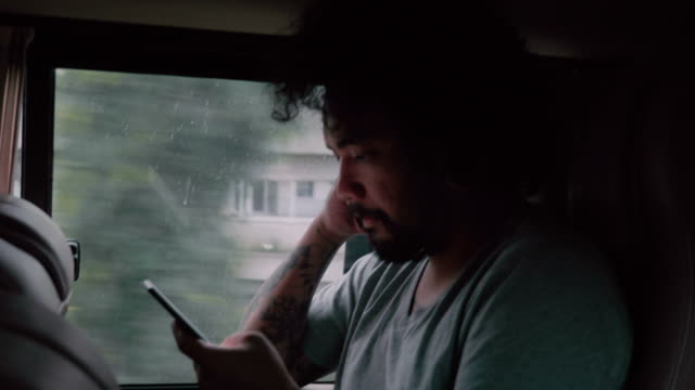vídeos y material grabado en eventos de stock de hombre asiático de smartphone que usa en coche. - asiento de atrás