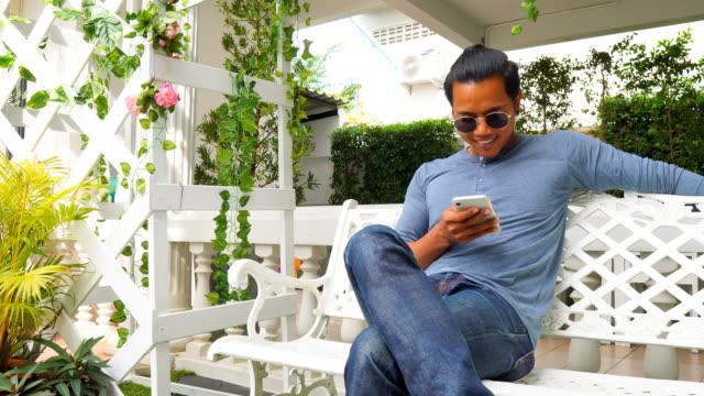 asiatischer mann mit smartphone im garten - one man only stock-videos und b-roll-filmmaterial