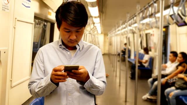 vídeos de stock, filmes e b-roll de homem asiático usando o smartphone em um trem - transporte público
