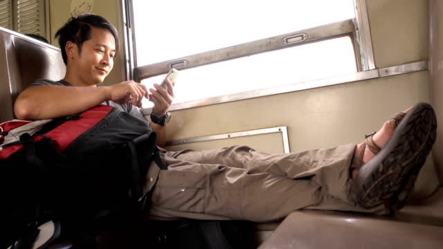 asian man using smartphone on train - bag stock videos & royalty-free footage
