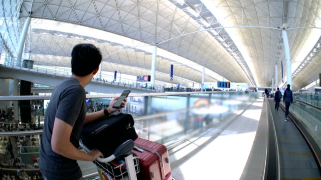 asian man using smartphone to check-in for his flight in airport - elevated walkway stock videos & royalty-free footage