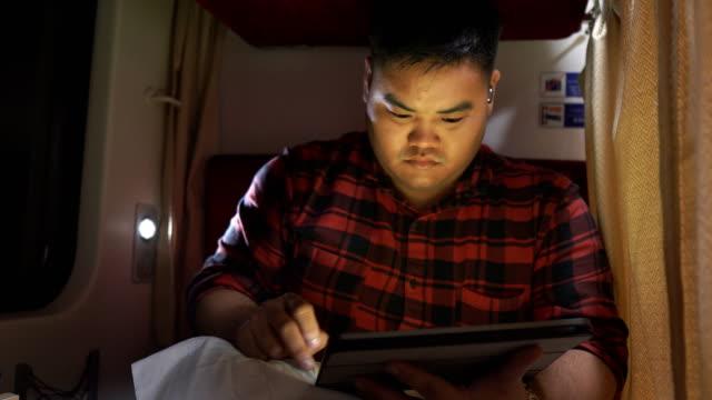 vídeos de stock e filmes b-roll de asian man using tablet,touch pad in train - nerd
