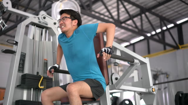 asian man using training machine for tricep arm muscles work out at gym - slim stock videos & royalty-free footage