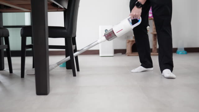 asian man using vacuum cleaner for cleaning the floor at home. - vacuum cleaner stock videos & royalty-free footage