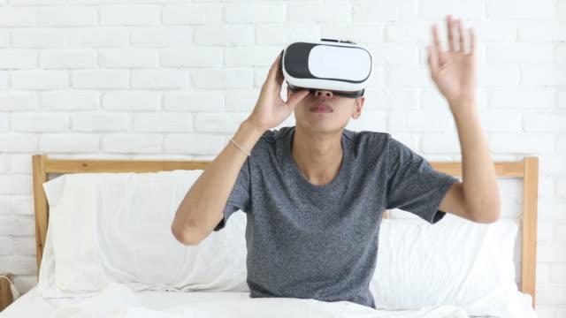 asiatischer mann mit vr im schlafzimmer - schutzbrille freisteller stock-videos und b-roll-filmmaterial