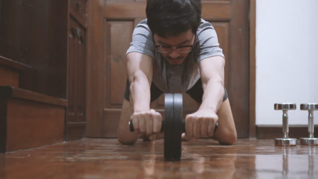asian man utilizing ab-wheel at home - bodyweight training stock videos & royalty-free footage