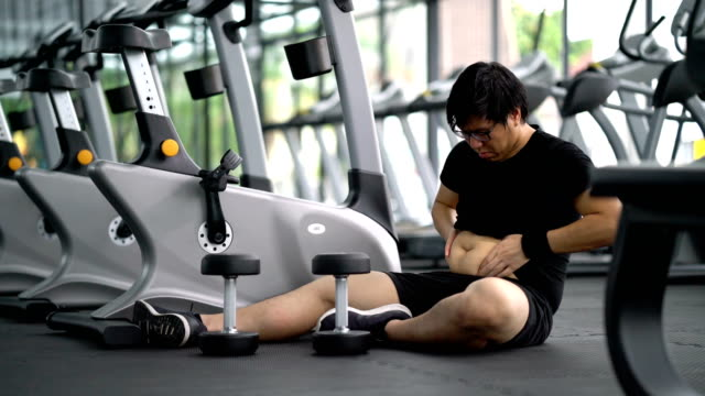 asian man very tired to lose his weight and remove the belly - fallimento video stock e b–roll