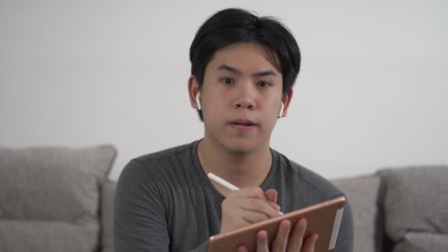 vídeos de stock e filmes b-roll de asian man video conferencing and writing notes, working from home - aula de formação