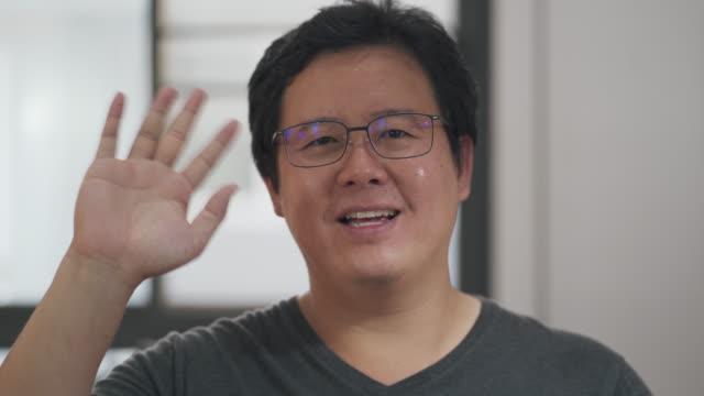 stockvideo's en b-roll-footage met aziatische man video conferencing hallo zeggen, werken vanuit huis - waving