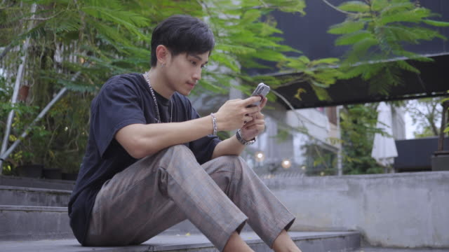 asian man waiting friend using smart phone in cafe - nomadic people stock videos & royalty-free footage